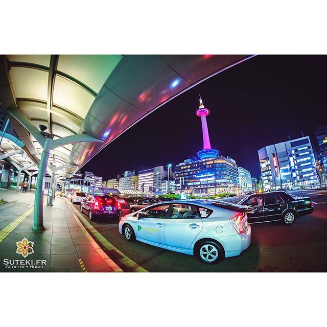 La valse des taxis devant une tour de Kyoto exceptionnellement habillée de violet