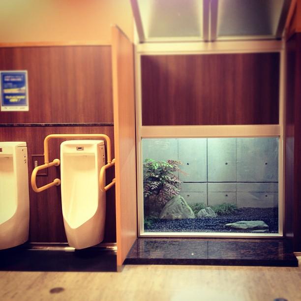Jardin intérieur japonisant dans les toilettes pour hommes d'une station service